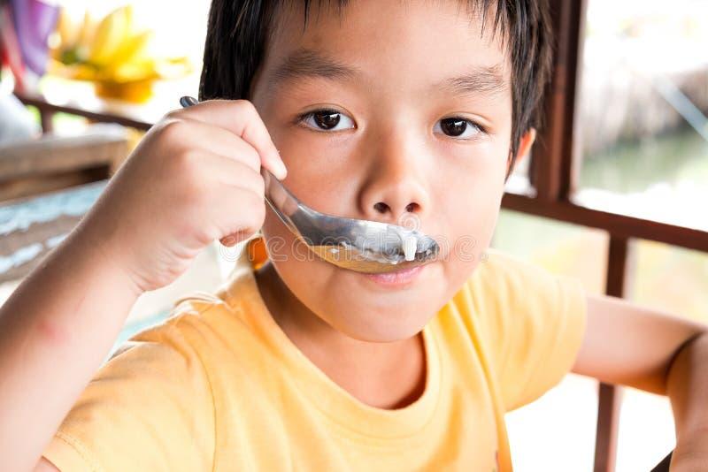 Een hongerige jongen zit bij de houten lijst voor eet dessert bij r stock foto's