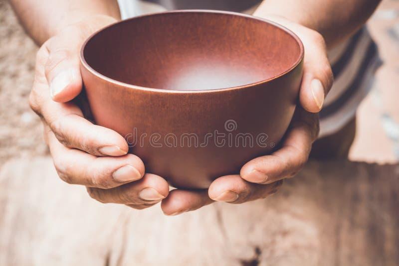Een hongerige mens die een lege kom houden stock afbeeldingen