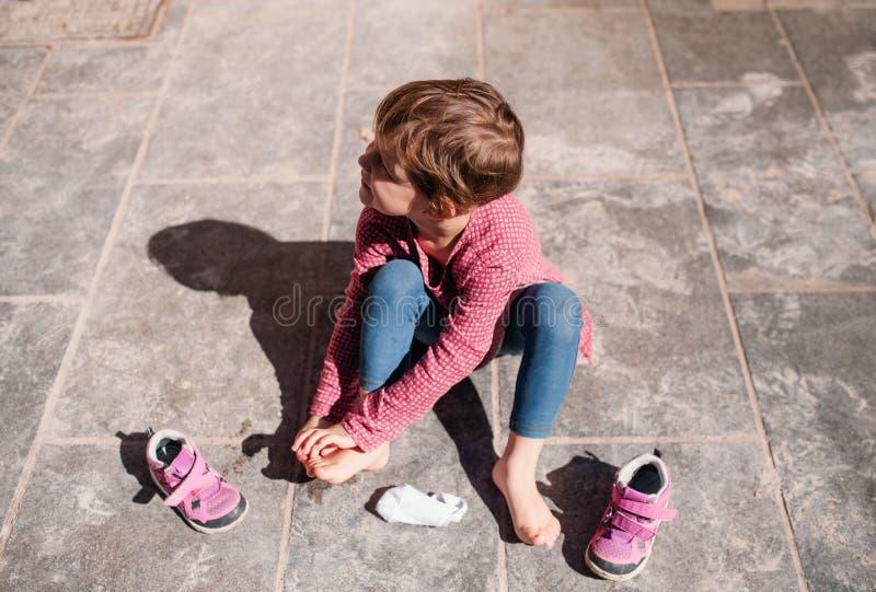 Een hoogste mening die van kleine meisjeszitting in openlucht op bestrating, schoenen van start gaan royalty-vrije stock fotografie