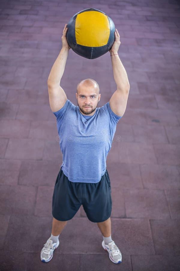 Een hoogste mening van de Atleet die de medische bal over zijn hoofd houdt royalty-vrije stock afbeeldingen