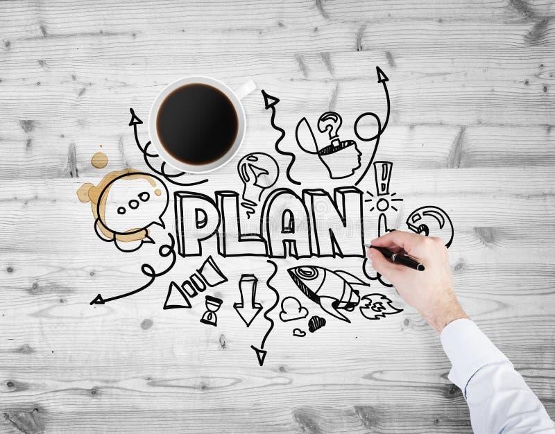 Een hoogste mening van een kop van koffie en een hand die een schets van het ontwikkelen van een nieuw businessplan trekt royalty-vrije stock fotografie