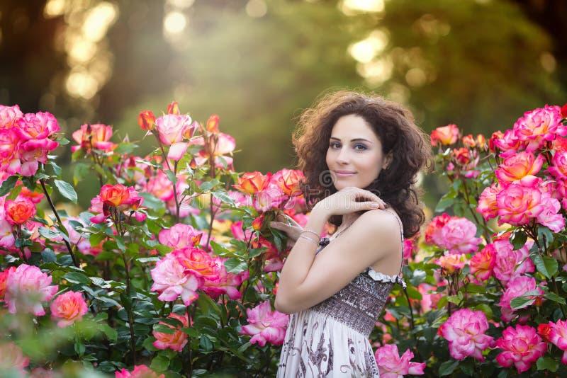Een horizontaal portret die van jonge Kaukasische vrouw met donker bruin krullend haar dichtbij roze roze struiken, aan de camera stock afbeelding