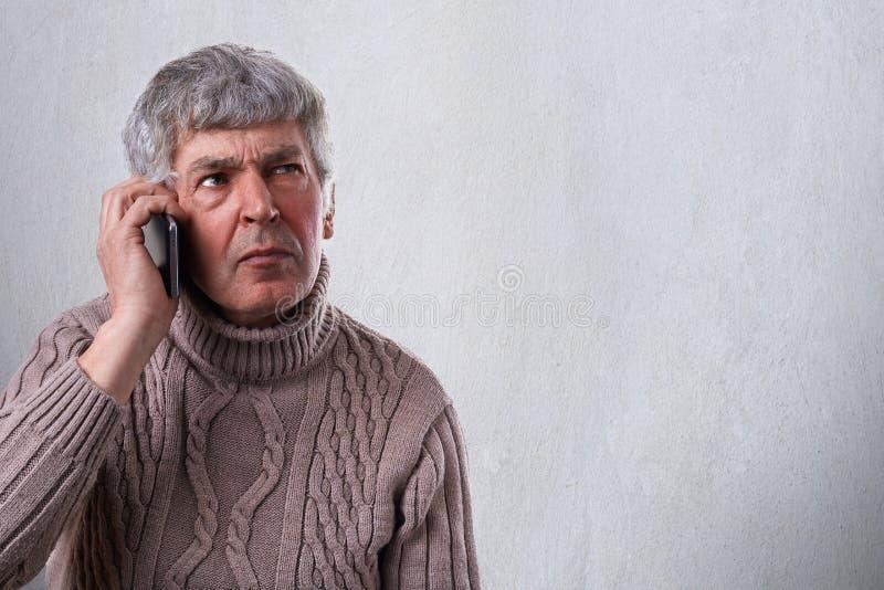 Een horizontaal portret van het ernstige, ongerust gemaakte, verstoorde rijpe mens talkiing op cellphone Een oude werknemer die s stock fotografie
