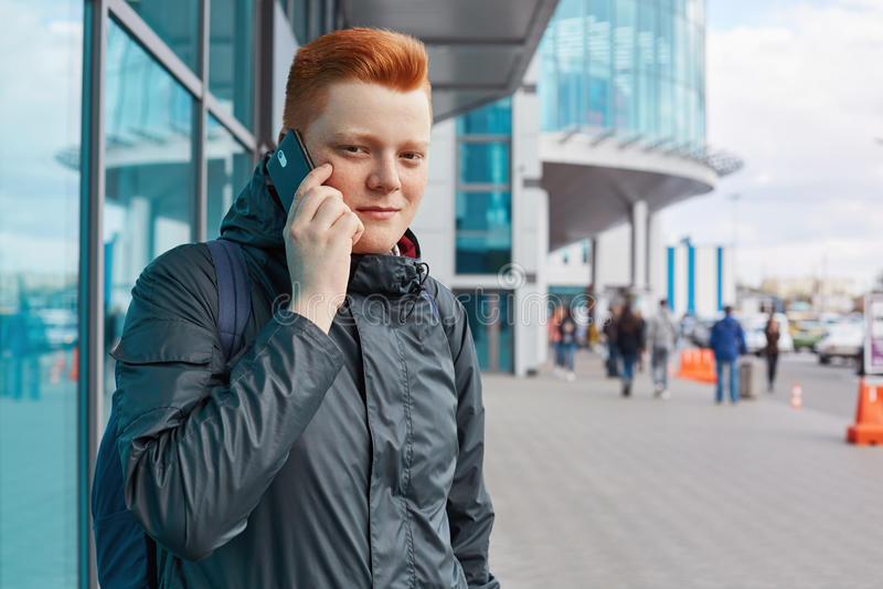 Een horizontaal portret van roodharigekerel met sproeten die jasje dragen en rugzak bij zijn het achter communiceren over mobiele stock foto's