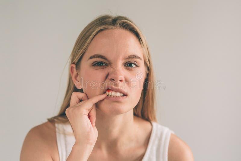 Een horizontale foto van een jonge ongerust gemaakte vrouw in geruit overhemd die aan sterke tandpijn en wat betreft haar wang li royalty-vrije stock foto's