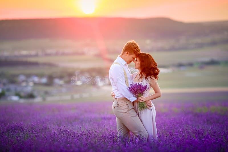 Een houdend van paar die zich in een lavendel gebied en het koesteren bevinden De mooie bruid kleedde zich in luxueuze huwelijksk royalty-vrije stock foto