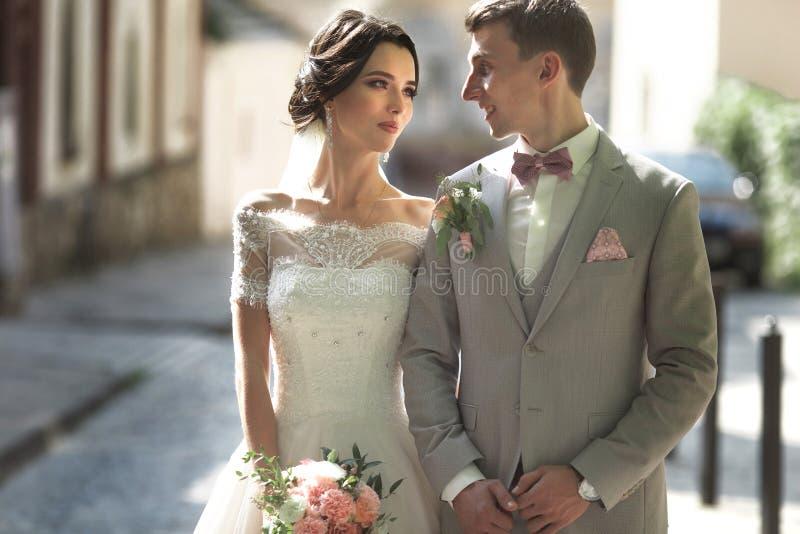 Een houdend van paar van jonggehuwden loopt in de stad, en glimlach De bruid in een mooie kleding, de bruidegom kleedde zich styl royalty-vrije stock afbeeldingen