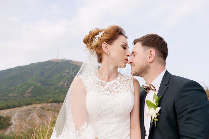 Een houdend van paar van jonggehuwden zit op de achtergrond van cityscape van een kleine toevluchtstad in de Kaukasus onlangs stock afbeeldingen