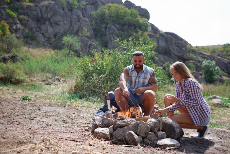 Een houdend van paar kweekte een brand op een picknick in het bos aan gebraden gerechtvlees Een meisje ontsteekt een brand in aar royalty-vrije stock afbeelding
