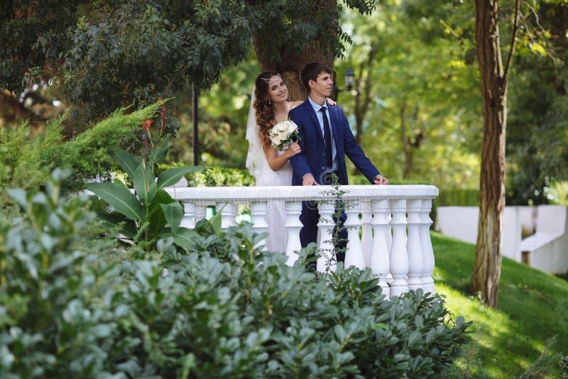 Een houdend van paar loopt in de tuin na de huwelijksceremonie De bruid en de bruidegom omhelzen en hebben pret de meisjesomhelzi royalty-vrije stock afbeeldingen