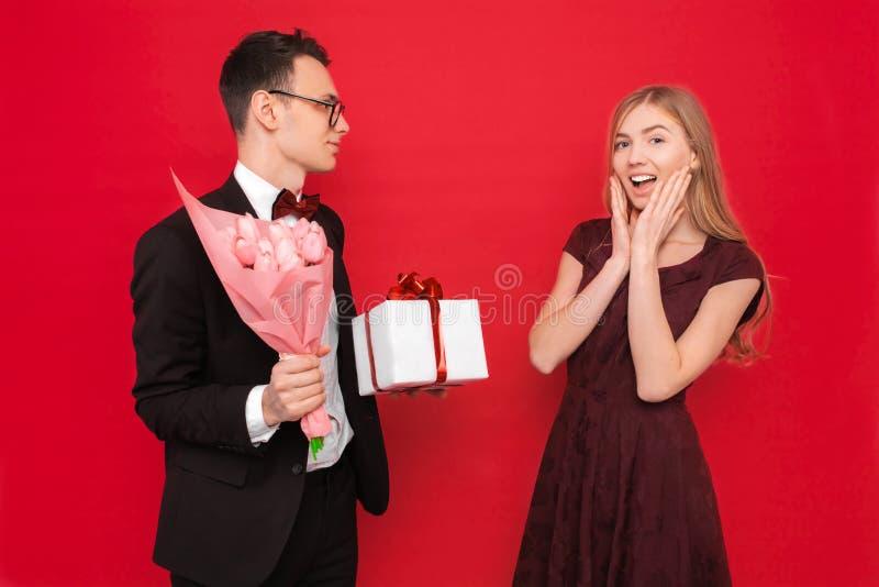 Een houdend van paar, een man geeft een geschokte vrouw een boeket van tulpen en een doos met een gift op een rode achtergrond De royalty-vrije stock afbeeldingen