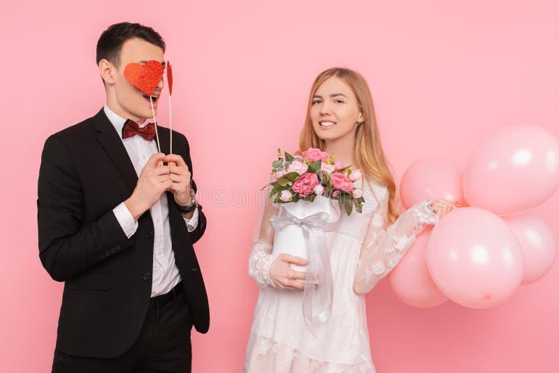 Een houdend van paar, een man twee document harten in zijn ogen houden, en een vrouw die een boeket van bloemen, op een roze acht royalty-vrije stock afbeeldingen