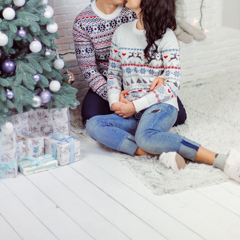 Een houdend van paar zit op de vloer dichtbij de Nieuwjaarboom royalty-vrije stock afbeeldingen