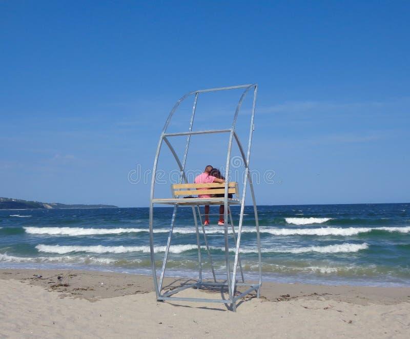 Een houdend van paar zit op een installatie van de strandredding tijdens een klein onweer stock foto's