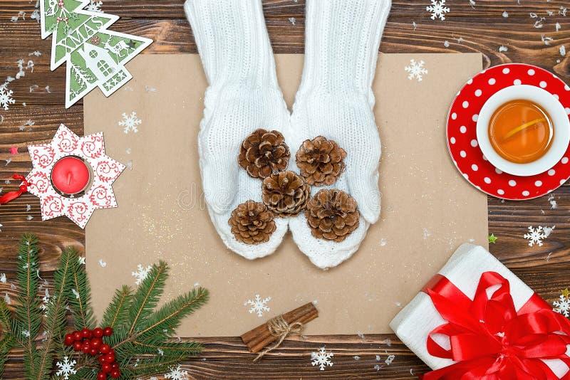 Een houten achtergrond met Kerstmisdecoratie Een vrouw in gebreide vuisthandschoenen houdt kegels De kaart van Kerstmis Nieuwjaar royalty-vrije stock fotografie