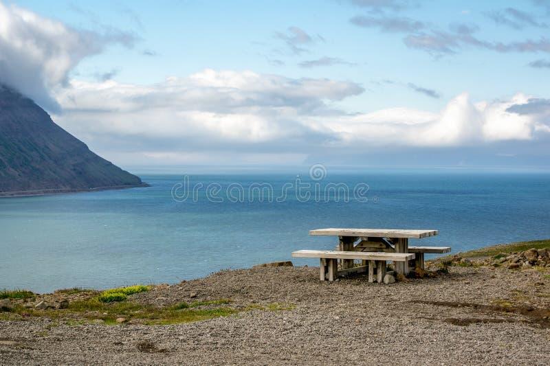 Een houten bank op een heuvel met mooie vooruitzichten in IJsland stock afbeelding