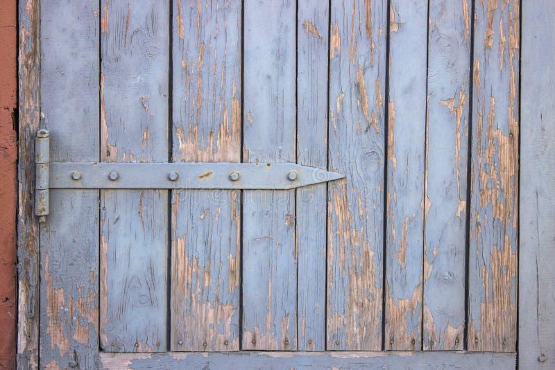 Een houten blind of een poort met het pellen van blauwe verf stock afbeeldingen