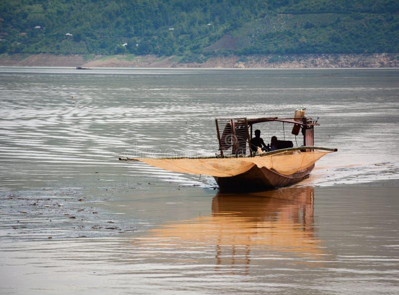 Een houten boot die op rivier met moutainachtergrond drijven in Moc CH stock afbeelding