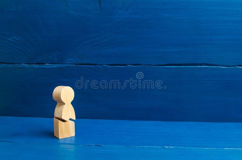 Een houten cijfer van een mens met een barst Het concept psychologische spanning en druk Kon niet zich onze zenuwen en onze gezon stock foto