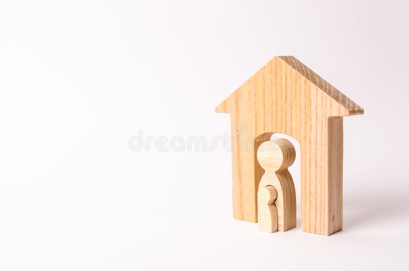 Een houten cijfer van een vrouw in een huis met een kind Het concept zwangerschap in vrouwen Zwangere Moeder Bevalling thuis stock afbeelding