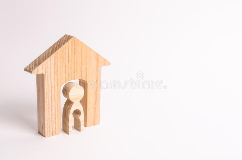 Een houten cijfer van een vrouw in een huis met een leegte binnen het lichaam in de vorm van een kind Het concept onvruchtbaarhei royalty-vrije stock foto's