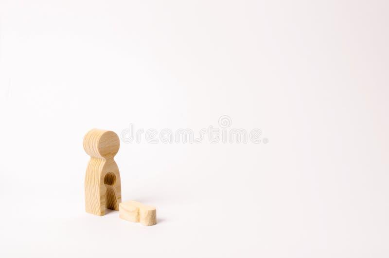 Een houten cijfer van een vrouw met een leegte waarvan een kind viel Het concept het verlies van een kind, abortus van zwangersch royalty-vrije stock afbeeldingen