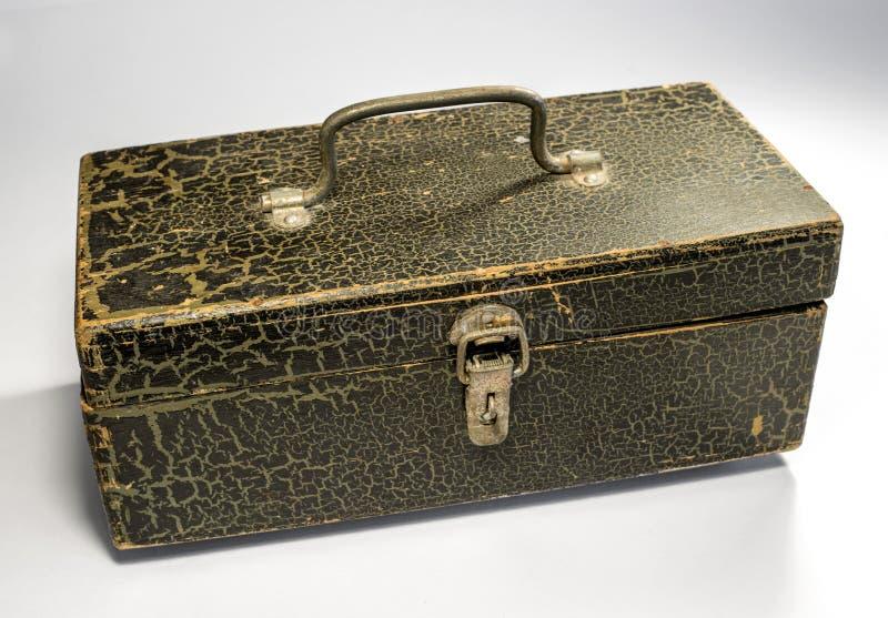 Een houten doos met een metaalhandvat en een klink op een lichte achtergrond De doos is geschilderd met verf, de gebarsten verf royalty-vrije stock afbeelding