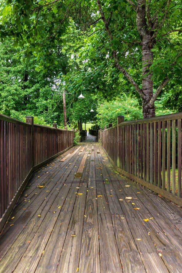 Een houten gangwinden door een bos en over een kreek stock foto's