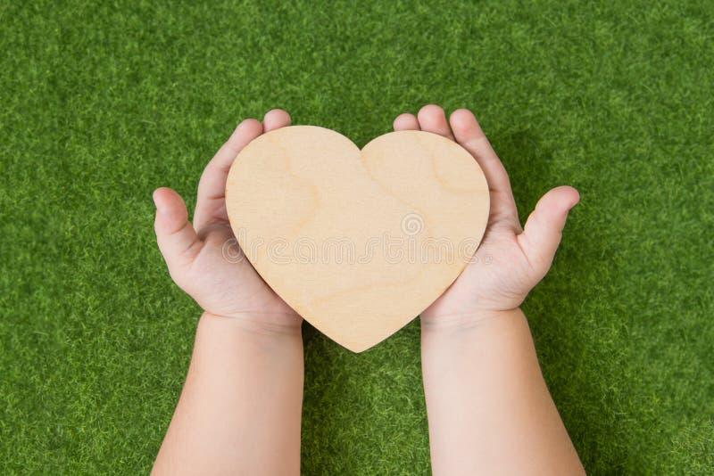 Een houten hart in de handen van een kind tegen de achtergrond van een groen gras stock foto's