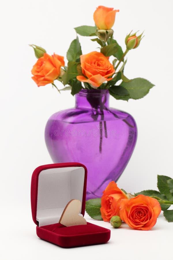 Een houten hart en een vaas van rozen stock afbeelding