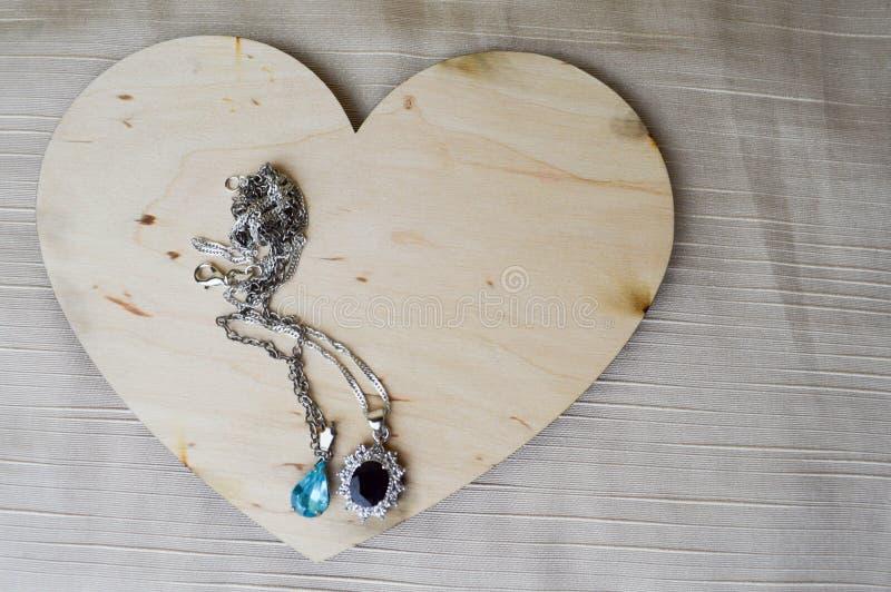 Download Een Houten Hart Voor De Dag Van Valentine ` S Met Zilveren Ornamenten, Kettingen Met Diamanten En Edelstenen Stock Afbeelding - Afbeelding bestaande uit hart, decoratief: 107701089