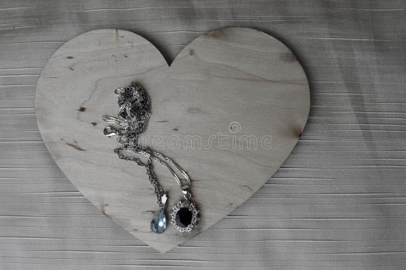 Download Een Houten Hart Voor De Dag Van Valentine ` S Met Zilveren Ornamenten, Kettingen Met Diamanten En Edelstenen Stock Afbeelding - Afbeelding bestaande uit juweel, toebehoren: 107701131