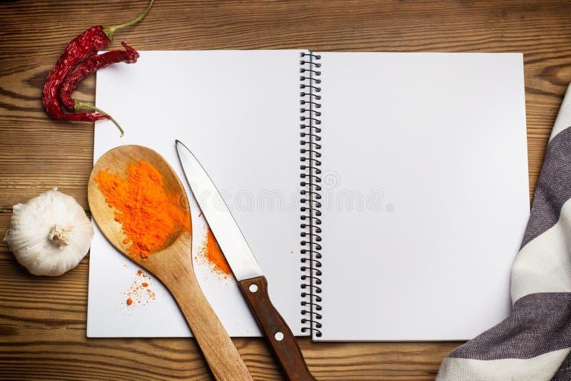 Een houten lepel met een knoflook en Spaanse pepers op een notitieboekje stock afbeelding