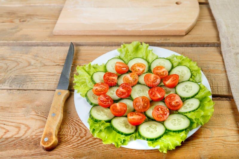 Een houten lijst aangaande een witte plaat is gesneden komkommers, tomaten stock afbeelding