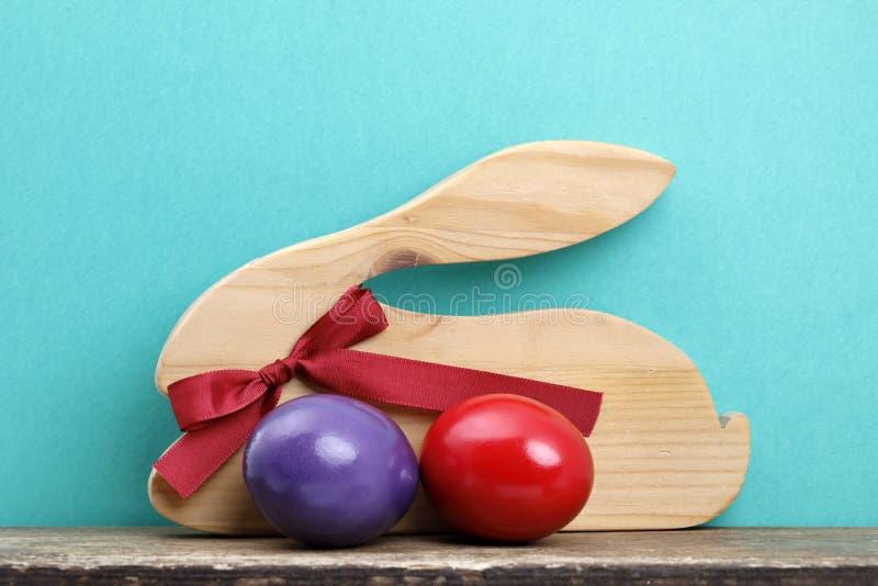 Een houten Pasen-konijn met rode lint en twee kleurde eieren op een raad royalty-vrije stock fotografie