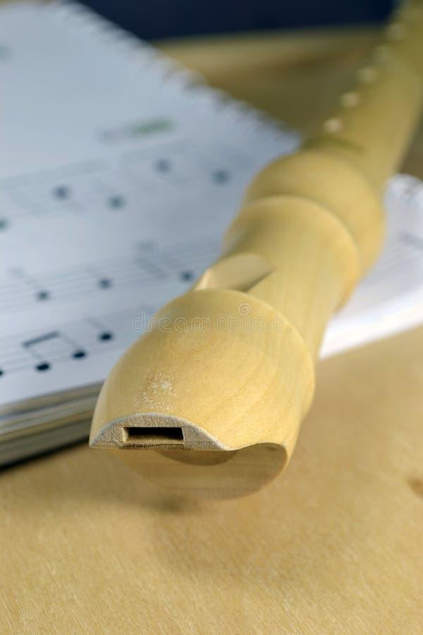 Een houten registreertoestel op bladmuziek. stock fotografie
