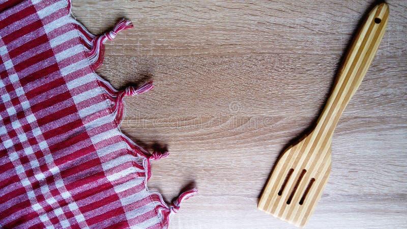Een houten spatel voor het roeren van gekookt voedsel Een keukentafellade van rood-wit gecontroleerd weefsel is op het recht royalty-vrije stock afbeelding