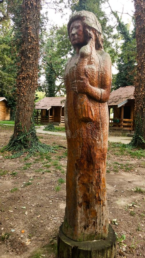 Een houten standbeeld die van een vrouw in een park, een vogel in haar hand houden royalty-vrije stock afbeelding