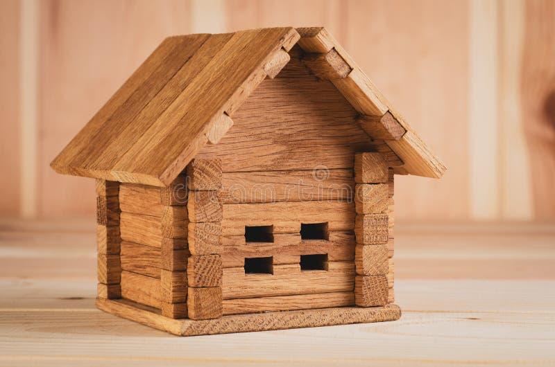 Een houten stuk speelgoed die huis vouwen schoot groot op een houten achtergrond stock foto