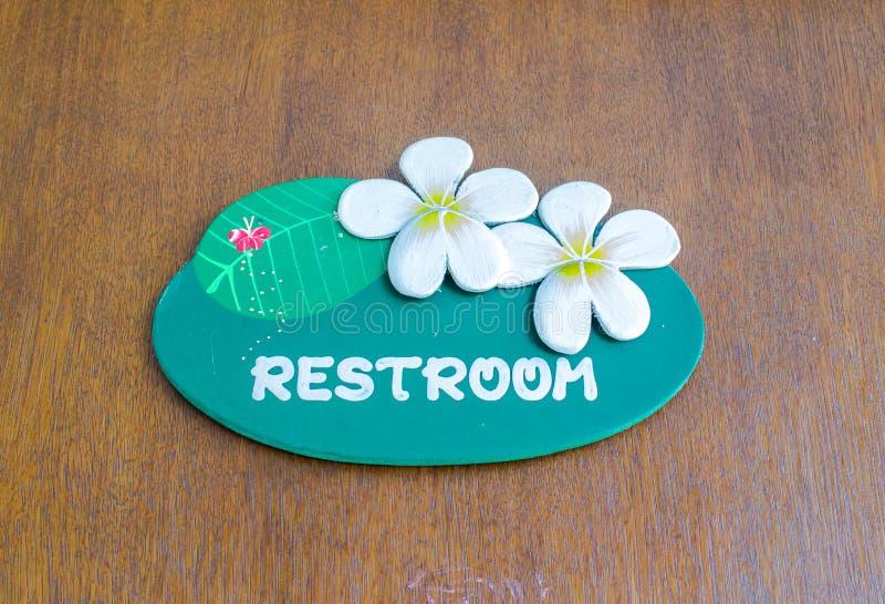 Een houten teken hing over de ingang aan een toilet stock afbeelding