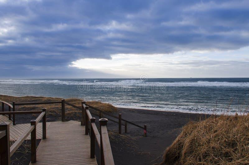 Een houten trap leidt tot een zwart vulkanisch zandstrand op de kusten van de Atlantische Oceaan royalty-vrije stock foto