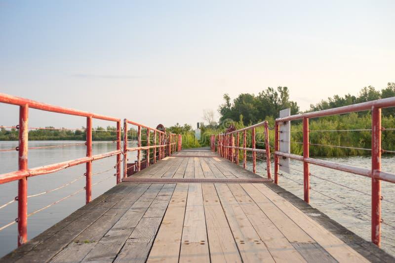 Een houten voetbrug over een waterweg stock fotografie