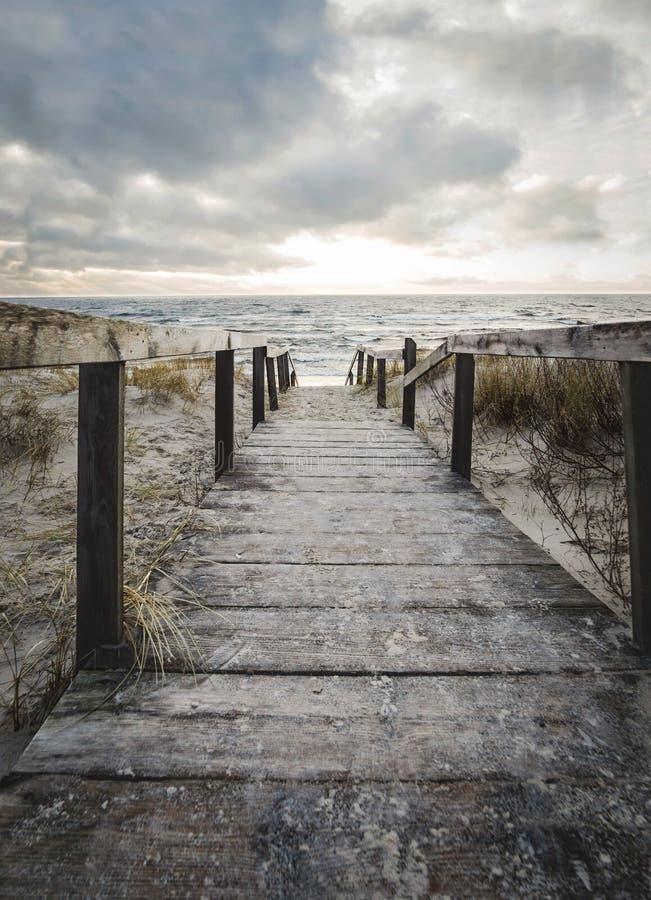 Een houten weg onder de duinen die tot de Oostzee bij zonsondergang in Klaipeda, Litouwen leiden royalty-vrije stock afbeelding