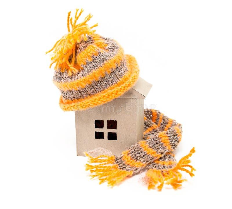 Een huis in een hoed met een sjaal stock afbeeldingen