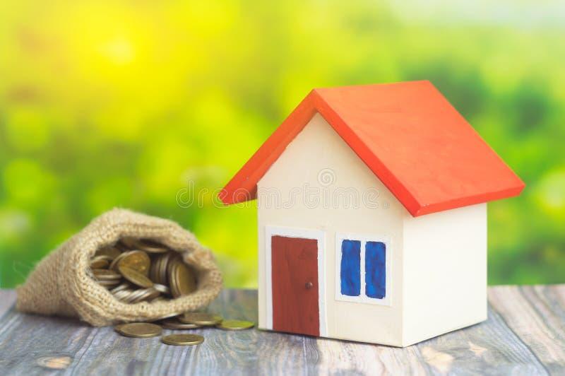 Een huis met rood dak op groene achtergrond met zak van zak met muntstukkengeld binnen concept van verkoopt of koopt huis stock fotografie
