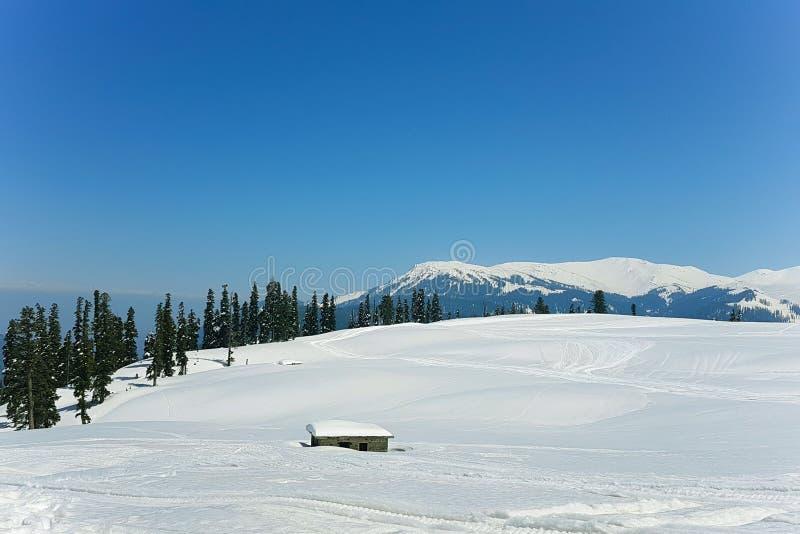Een huis onder de sneeuwvallei stock foto's