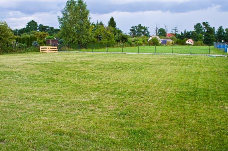 Een huisperceel met goed gehandhaafde gras en compostdoos in de hoek stock foto