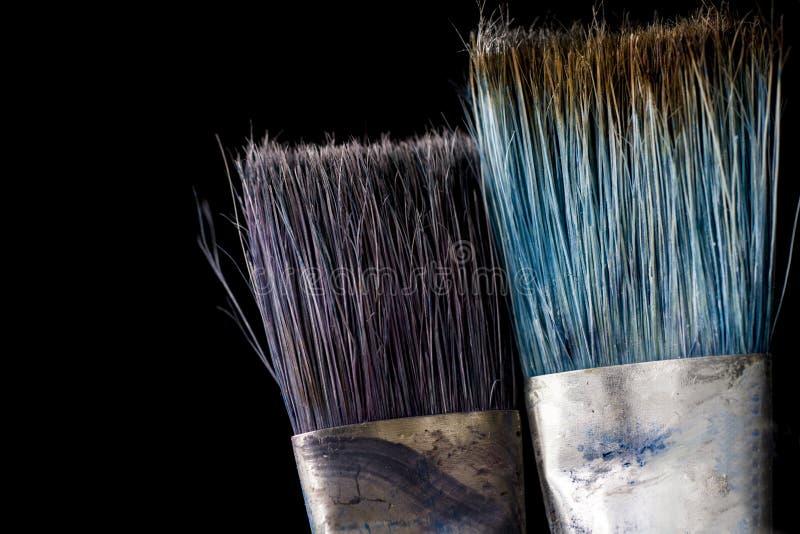 Een hulpmiddel voor het werk van de kunstenaar Twee borstels in verfclose-up op een zwarte achtergrond royalty-vrije stock fotografie