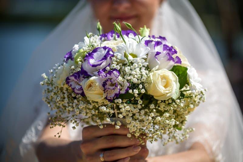 Een huwelijksboeket van lichte rozen in de handen van de bruid Beige en roze bloemen stock foto