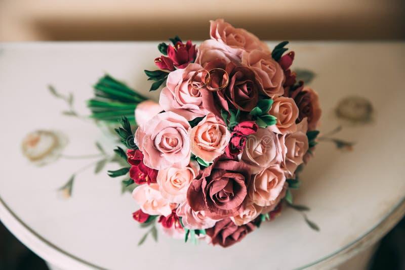 Een huwelijksboeket van rode en roze rozen ligt op een houten uitstekende lijst Gouden ringen van jonggehuwden op bloemen E stock foto's